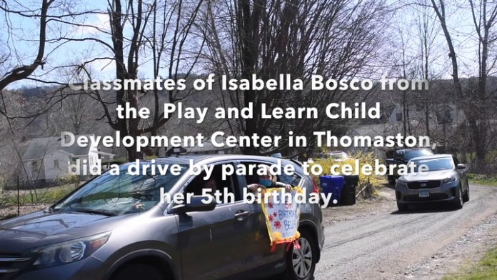 The classmates of a Thomaston girl participate in a drive by car parade by her home to celebrate her fifth birthday.