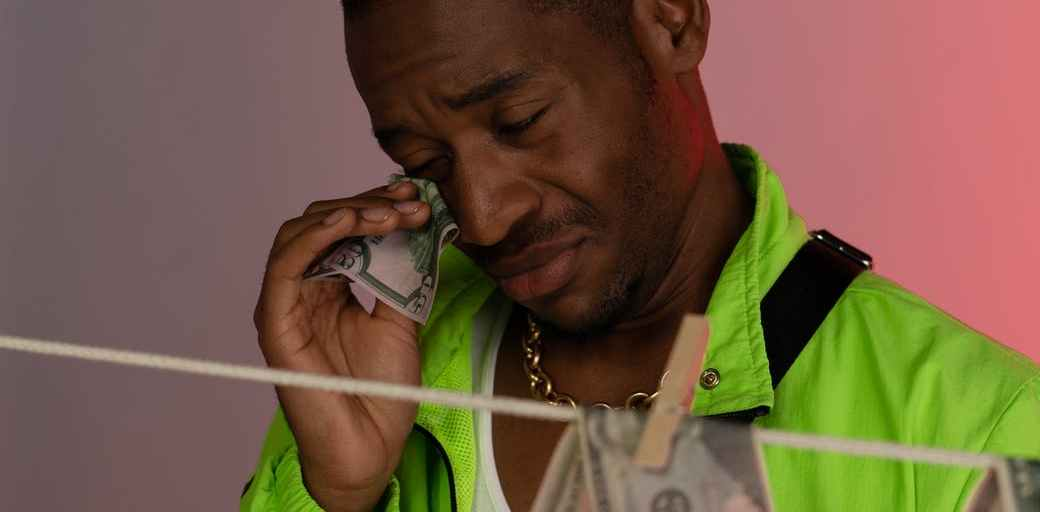 man in green jacket wiping his tears using banknote