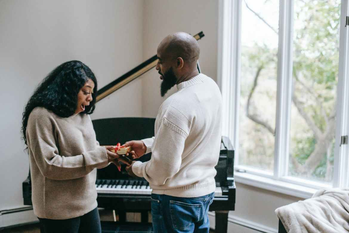 black man giving present to wife