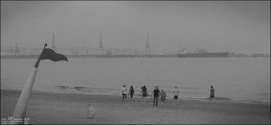 Paseantes en playa gris (I)