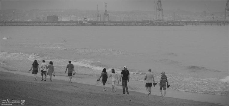 Paseantes en playa gris (II)