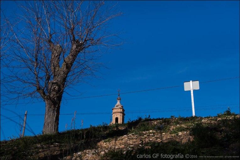 Cartel, iglesia y árbol