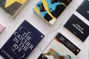 arrangement of soft cover books placed in row on white marble surface