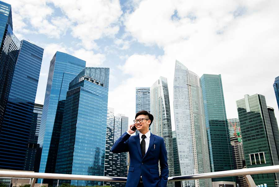 Asian businessman one the phone in front of buildings
