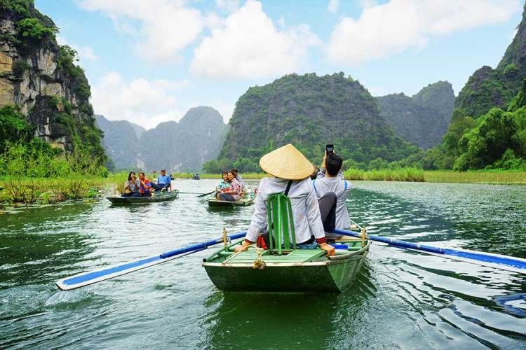 Tourists traveling in small boat along Ngo Dong River, Vietnam