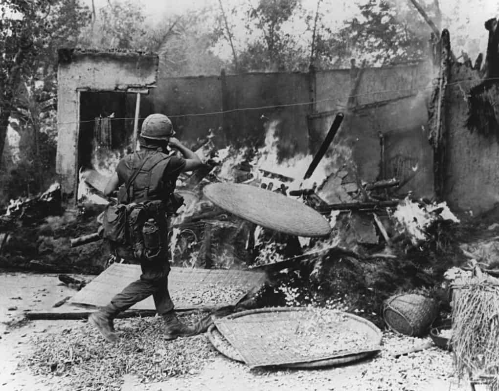A US soldier stands next to the aftermath of the My Lai Massacre.