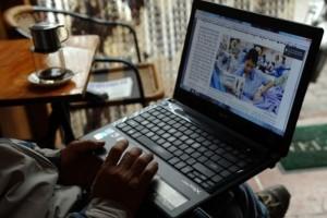 Bức hình chụp ngày 15/1/2013. Một người đàn ông đang đọc tin trên mạng bằng laptop trong một quán cafe ở Hà Nội. Sau khi sách nhiễu và bỏ tù đã không thể làm cho giới blogger im lặng, chính quyền cộng sản đã bắt đầu xây dựng đội quân đi tuyên truyền, xâm nhập vào các chatroom và hát những bài hát ca ngợi chế độ.  AFP PHOTO/HOANG DINH Nam
