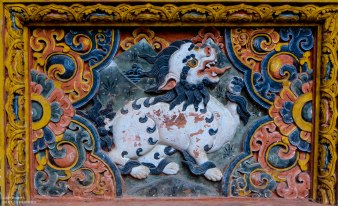 mythical Snow Lion painted in traditional Bhutanese style on the wall of a house.