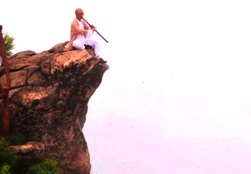 A kungfu hermit playing his flute from the top of a cliff in a crisp autumn air