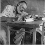 Ernest Hemingway writing at a campsite in Kenya