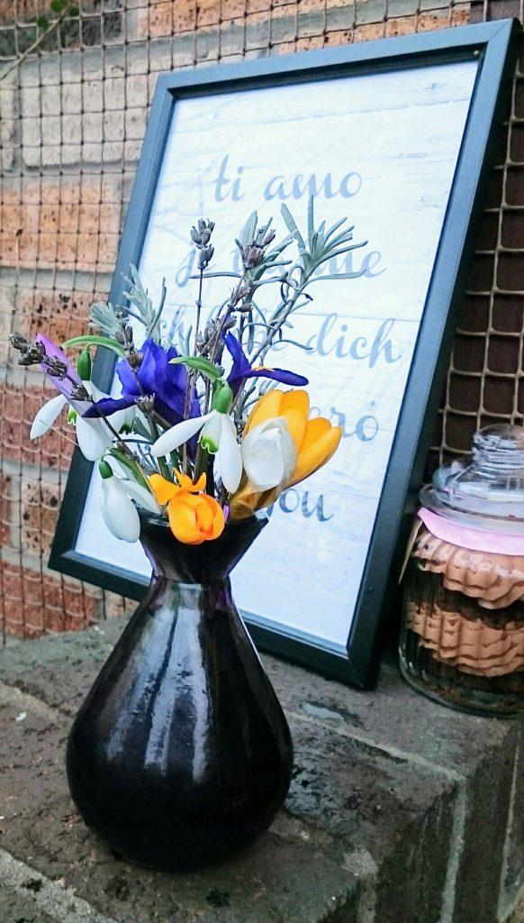 ris, crocus, snowdrops, lavender in a purple glass vase