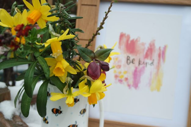 tete a tete daffodils, cotoneaster in a bee covered jug with a Pink yellow 'be kind' sign