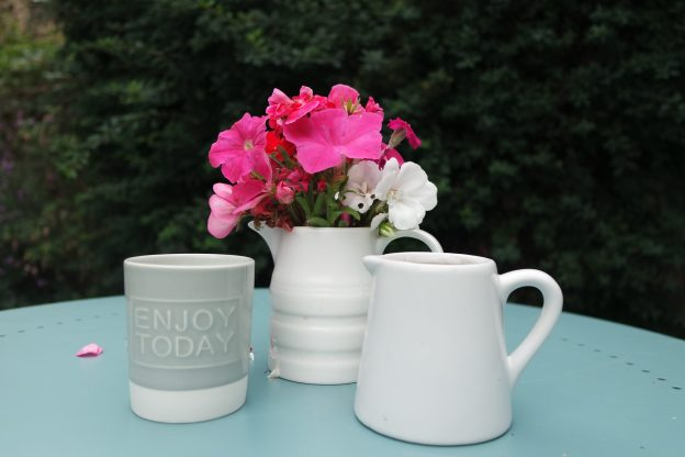 white jug with pink, pelargonium campion and petunia with a jug and a candle enjoy today