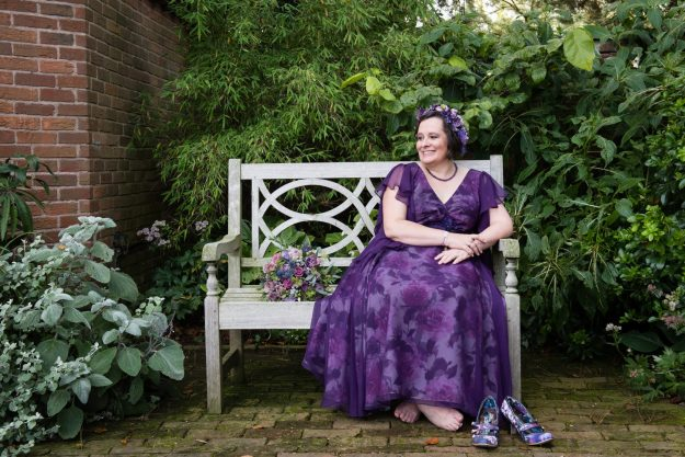 me sitting on bench in my purple floral wedding dress