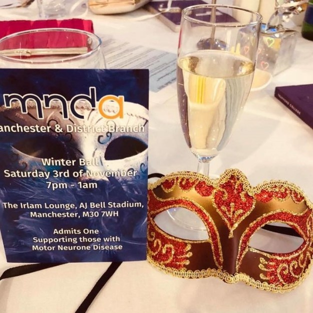 blue ticket for Motor Neurone Disease Association Manchester Ball - 3 Nov 2018 with orange mascarade mask on a party table