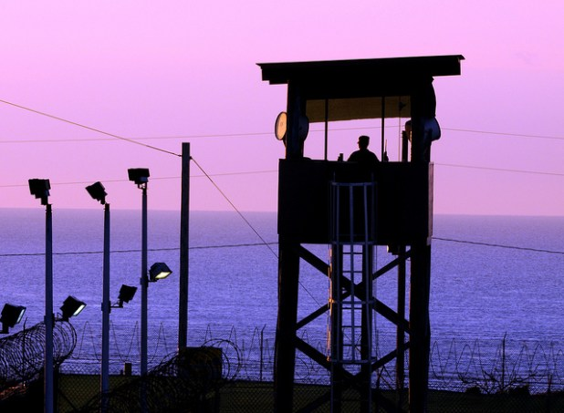 A member of Puerto Rico Army National Guard guards her post over the Joint Task Force Guantanamo detention facility at sunrise. (Photo by The National Guard, Creative Commons License)