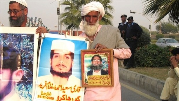 "Muhammad Ibrahim Khan, 85, from Jalalpur, Punjab, holds up pictures of his son, 18 year old Muhammad Zubair, who was picked up by security forces on 9/11/2009. ""He was our only child, and was just married,"" Khan said. ""At least tell us what he was charged with. We don't even know if he is alive or dead."" (Photo by Umar Farooq via IRIN)"