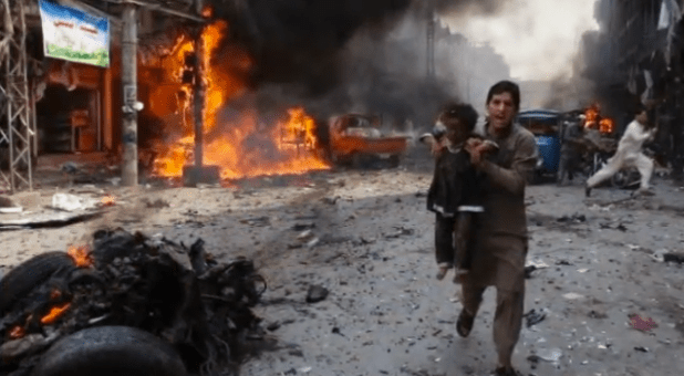 A man rescues a child after a bomb explosion in Peshawar, Pakistan, in September 2013. (Photo from video)