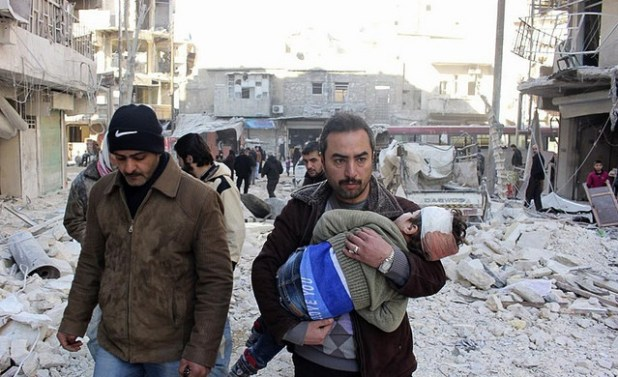 A man carries an injured child after a Syrian army attack on northwestern Syrian city of Aleppo. (Photo by Freedom House, Creative Commons License)