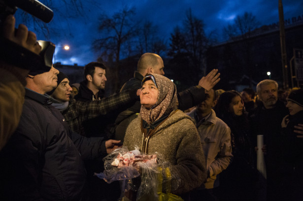 An elderly woman presents discarded pieces of raw meat during a protests in Sarajevo on February 8, 2014, outside the city's municipal building. It sustained heavy damage after protesters attacked and set fire to it. (Photo by Jodi Hilton, via WNV)