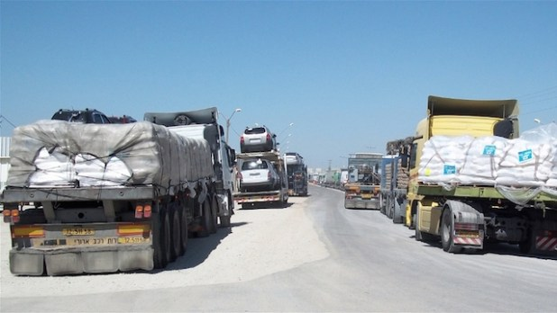 Truckloads of humanitarian aid and commercial goods bottle-necked at Kerem Shalom crossing along the Gaza-Israel border.  (Photo by Erica Silverman/IRIN)