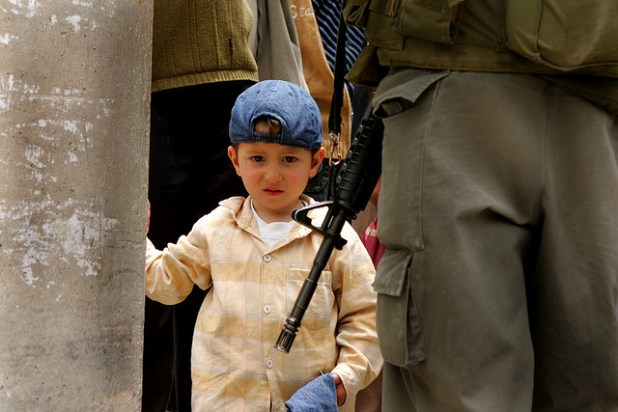 A Palestinian boy looks at the gun of an Israeli guard at Abu Dis; check post in East Jerusalem. (Photo by Kashfi Halford, Creative Commons License)