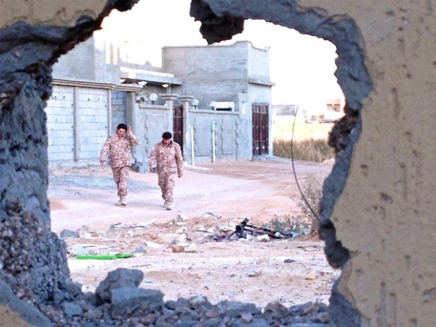 Two soldiers from forces operating under Libya's Tripoli-based government walking through the deserted streets of Bin Jawad, seen through a hole blown in the outside wall of a family home. (Photo by Tom Westcott/IRIN)