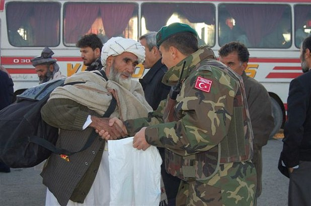 A Turkish soldiers greets Hajj pilgrims from Afghanistan. (Photo by isafmedia, Creative Commons License)
