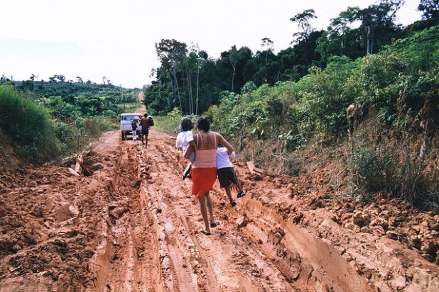 A family makes its way down a mud-filled road in Vila Da Canpas in the Amazon region of Brazil, near Manaus. For many, the only transportation available is by foot. Brazil. (Photo by Julio Pantoja / World Bank, Creative Commons License)