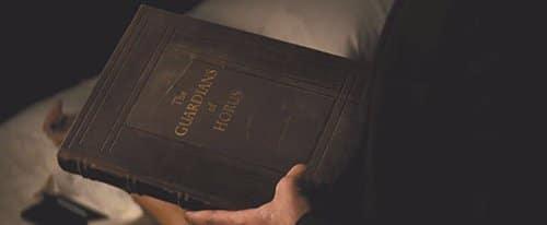 """No filme, um dos livros usados para pesquisar o olho é chamado de """"Os Guardiões de Horus""""."""