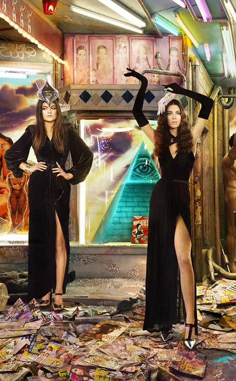 "The sister on the left wears a vulva-shaped headdress making her look like some kind of priestess. They stand on a pile of ""celeb-worship"" magazines, mountain of garbage on which their careers are built on (Kanye depicted as Jesus on the cover of Rolling Stones part of it). Behind the sisters (at the base of the pyramid) is an almost ironic box of Wheaties featuring Bruce Jenner when he was an Olympic athlete."