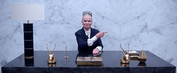 A woman points Rihanna towards another room. On her desk are two horned heads (Baphomet) and a pyramidal thing. She is in the offices of the higher-ups of the elite, where their true symbols are out in the open.