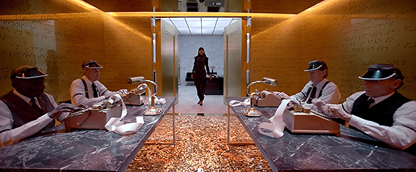 Rihanna opens the heavy doors of a room with walls of gold with braille reliefs (the language of the elite). On the floor, a whole bunch of coins.