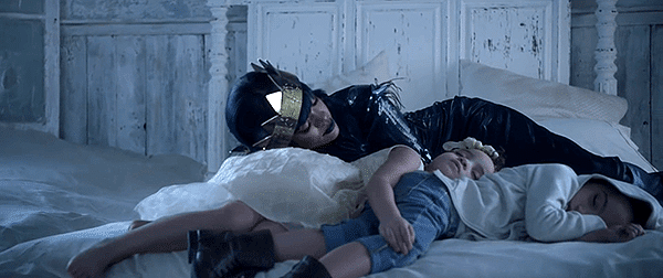 Crowned Rihanna finds the dualistic kids sleeping on her bed. Laying on them, her transformative process is completed.