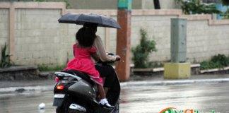 Bajo la lluvia, una mujer y una niña se desplazan en una pasola por una calle de Elías Piña, dónde las precipitaciones se han vuelto frecuentes en los últimos días. (Foto: Genris García)