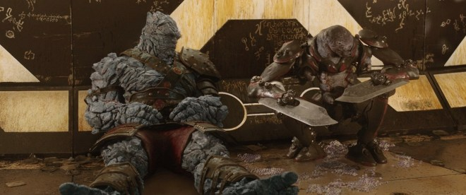 Korg, an large gray rock-person, inquiring about the secretions coming out of Miek, a grub-like being in a metal exoskeleton with knives for hands.