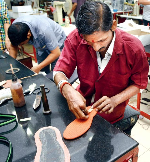 Another worker puts new soles on old footwear for better use
