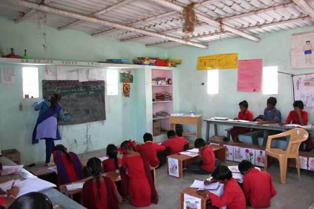 Children of three separate grade levels sitting in one classroom