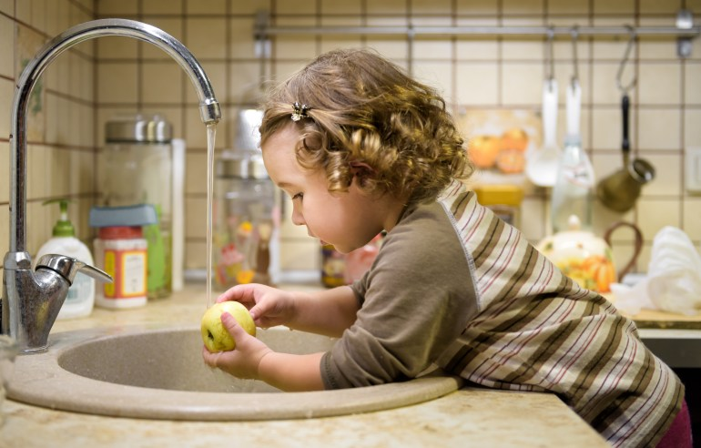 Little girl washes an apple
