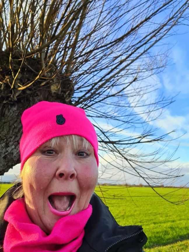 Annicka med mössa vid ett pilträd