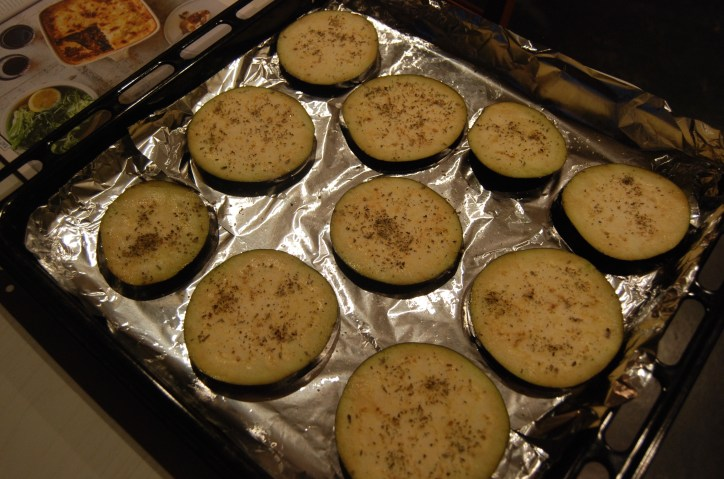 eggplant slices topped with oregano ready for the oven