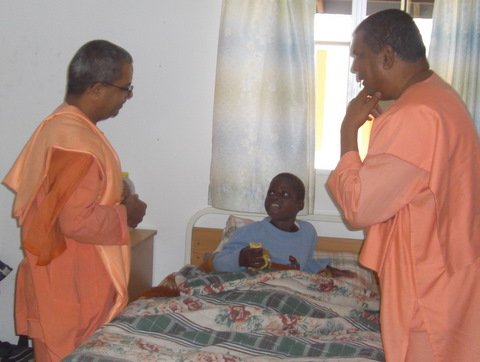 The visiting Swami Virabhadanndaji with Swami Saradaprabhanandaji at Abandi Home talking to a terminally ill patient