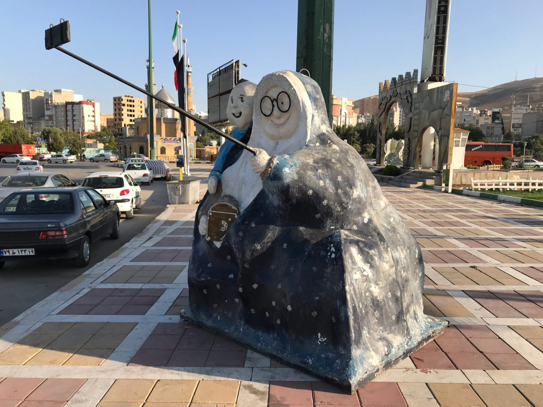A statue in Kermanshah. A woman wearing a chador and holding her grandson uses a selfie stick to take a selfie | VincePerfetto.com