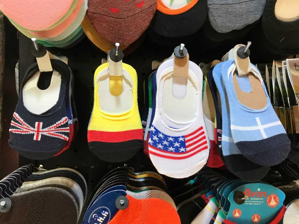 Seen in the Kermanshah Bazaar. From left to right: baby socks with the flags of Britain, Germany, America, and Greece (although, I could be wrong about the Greece flag). Pictures of the American flag inside Iran - and United States military merchandise, too! | VincePerfetto.com