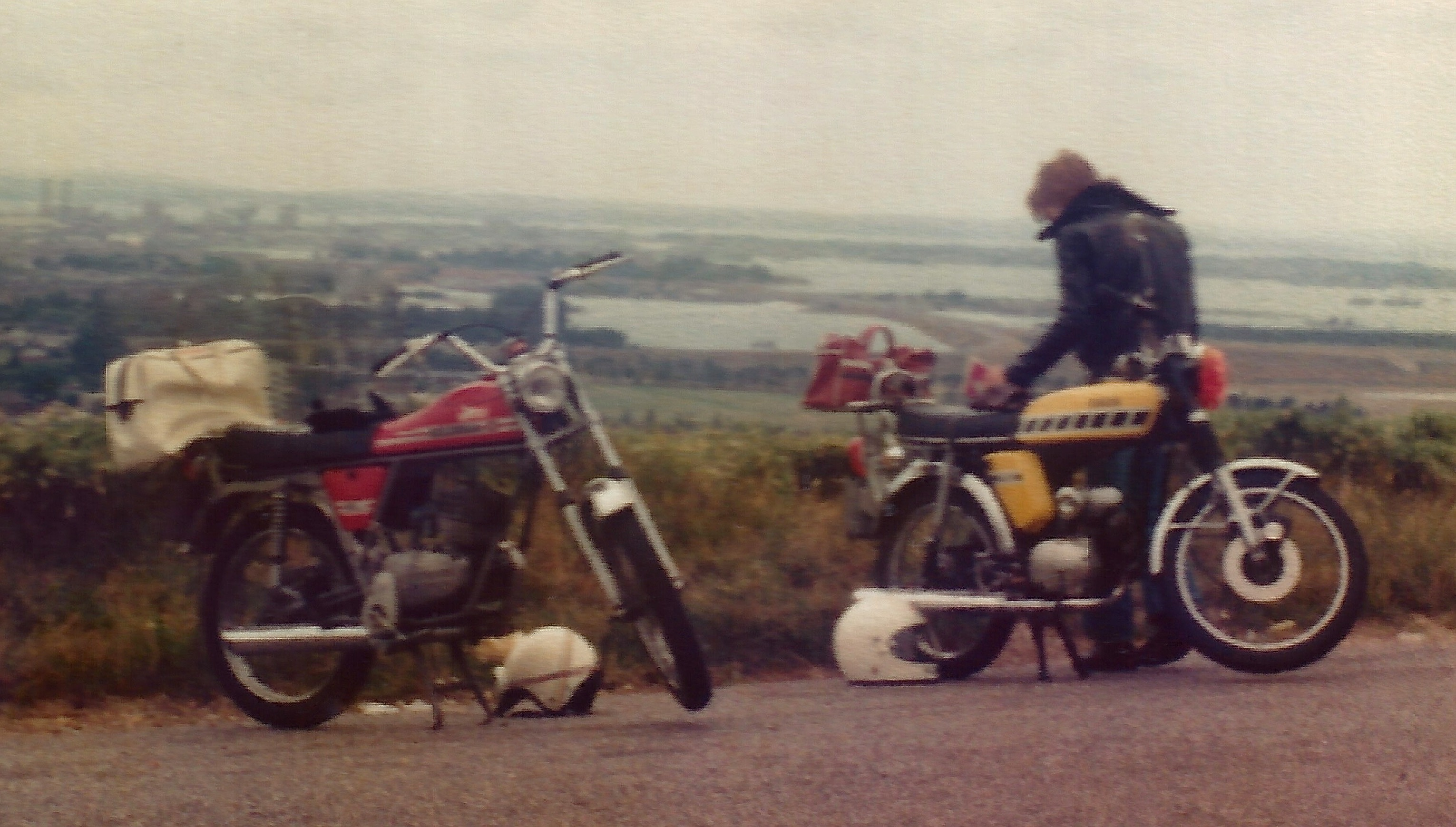 The Gilera 50 moped parked on a hill view next to a yellow Yamaha FS1E with it's owner Jeff