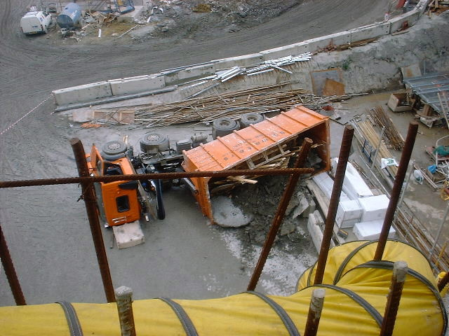 Photograph of a tipped construction lorry laying beside a tall crane on a building site