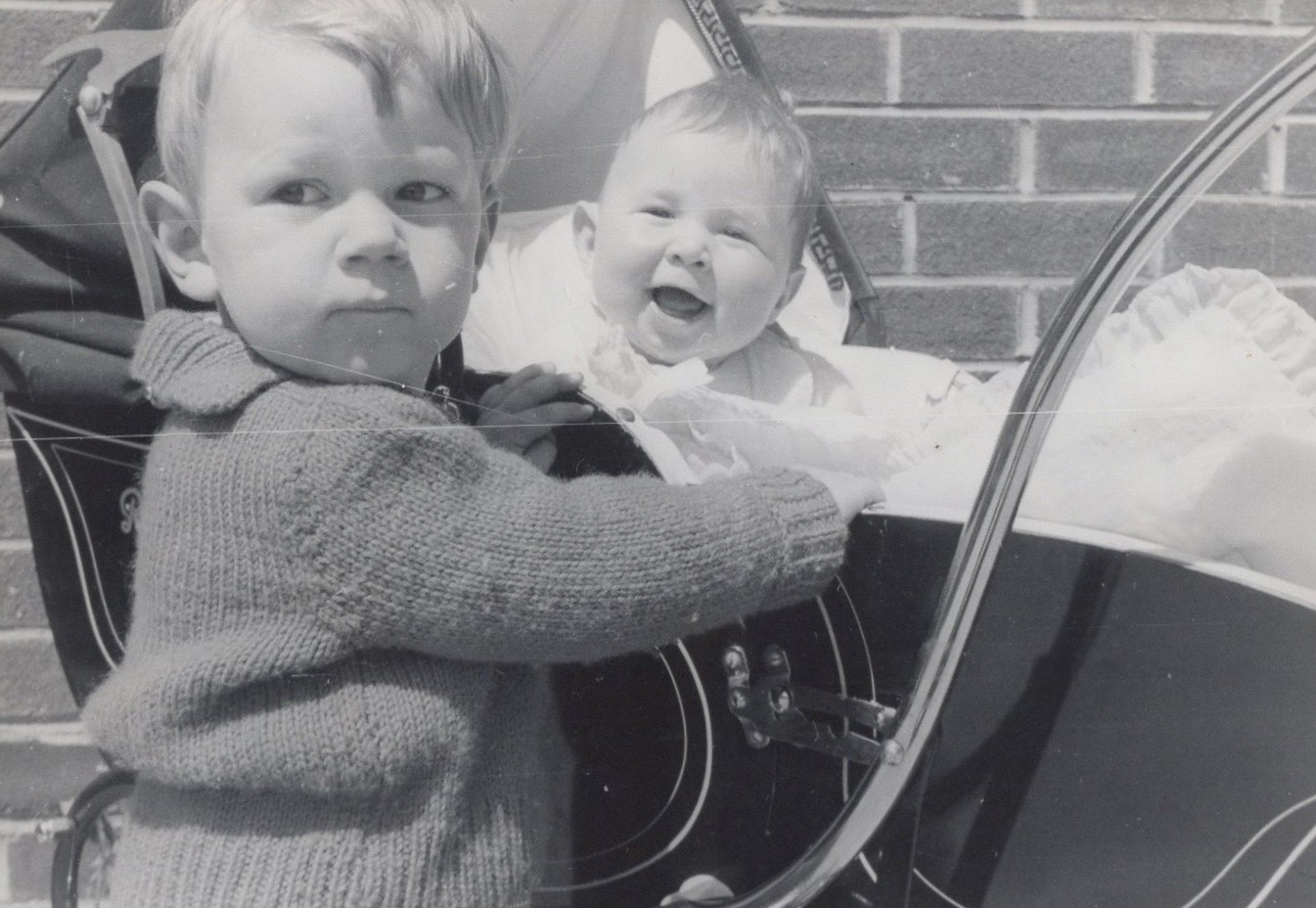 Black and white photograph of Mark stood next to Vince Poynter in a pram