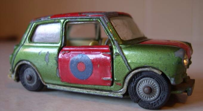 A close up photograph of toy green classic mini in a rather tatty state with red overpainted opening doors, bonnet and roof with a blue circle logo on the door