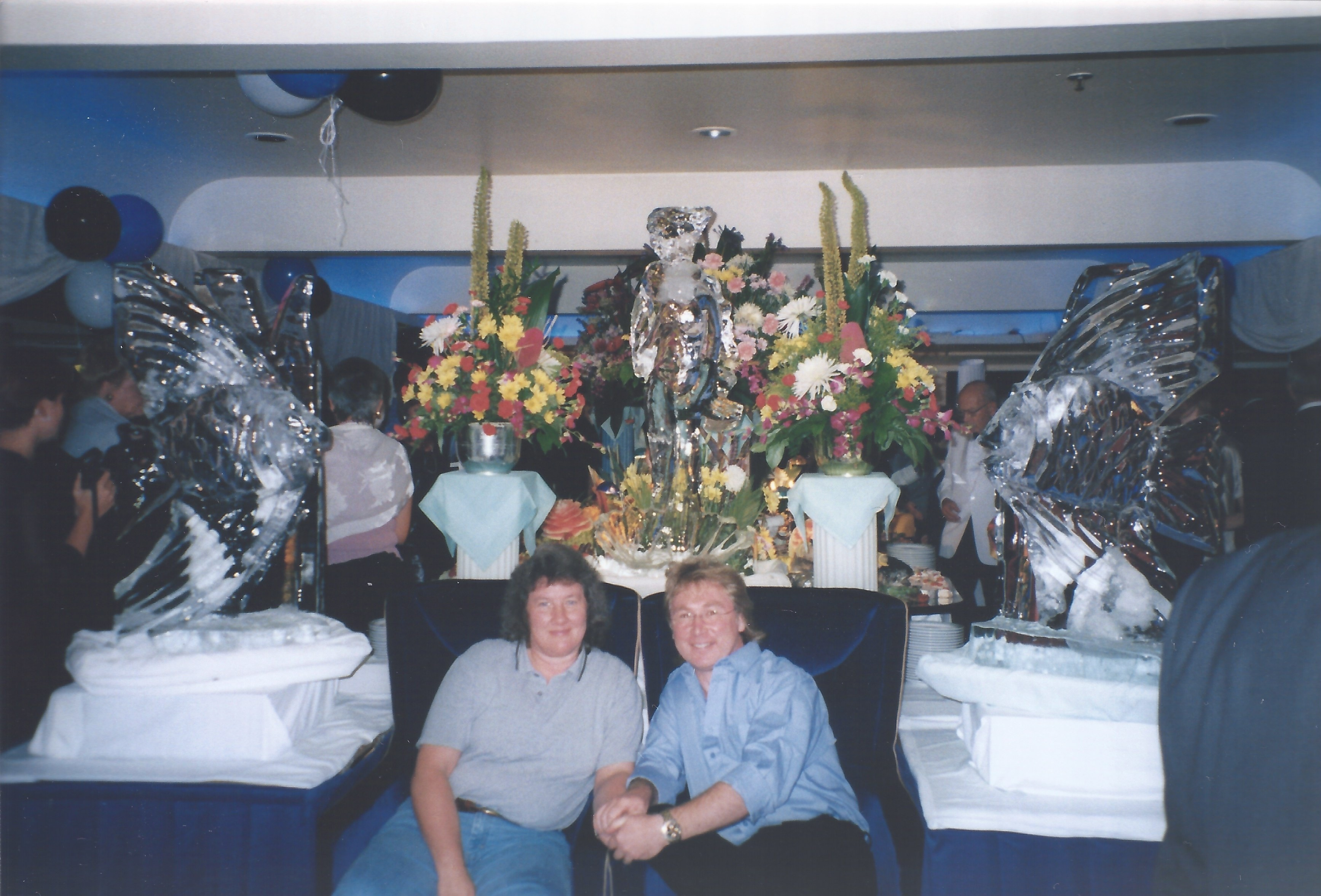 Photograph of the author and his wife sat in front of three large ice carvings
