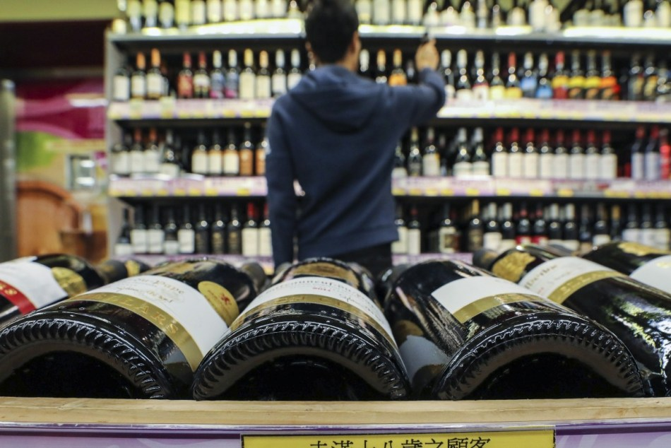 Hong Kong wine buyer picking out wines at a wine shop (pic: file photo)